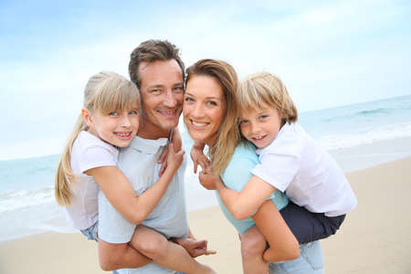 sons: Parents giving piggyback ride to kids at the beach Stock Photo