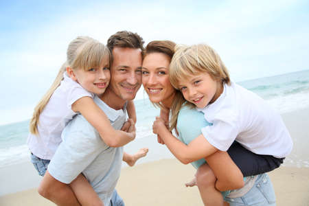 blonde mom: Parents giving piggyback ride to kids at the beach Stock Photo