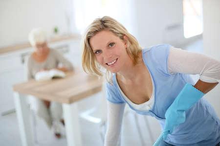 gospodarstwo domowe: Młoda gospodyni czyszczenia podłogi w domu seniorów