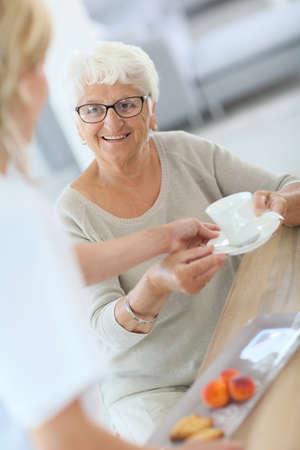 Homecarer giving tea to elderly woman photo