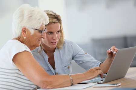 Homecarer with elderly woman using laptop computer photo