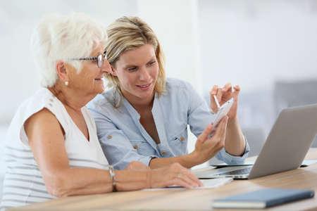 teaching aid: Homehelp with elderly woman using smartphone