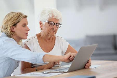 impuestos: Homecarer con mujer mayor que usa el ordenador portátil Foto de archivo