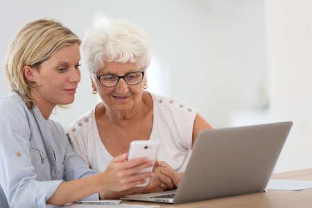 Startseitehilfe mit älteren Frau mit Smartphone Standard-Bild