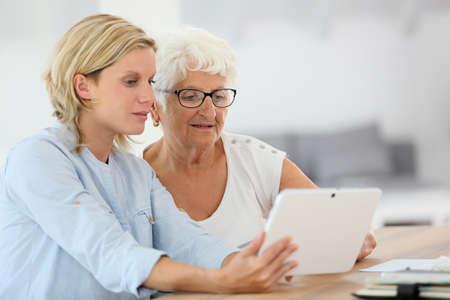 デジタル タブレットを使用して高齢者の女性とホームヘルプ 写真素材