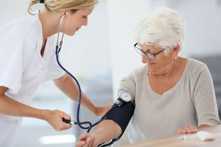 Doctor checking elderly womans blood pressure Stock Photo