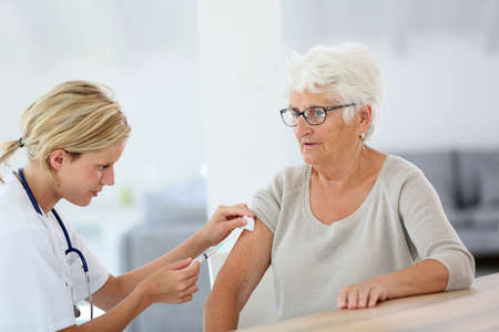 Nurse making vaccine injection to elderly patient Stock Photo