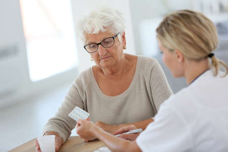 doctor giving pills: Doctor giving pills to elderly woman Stock Photo