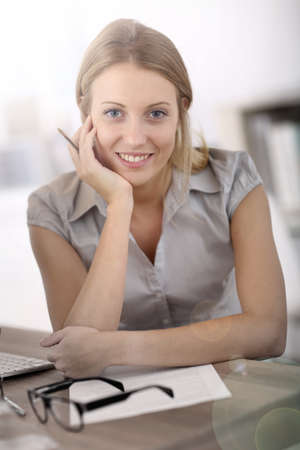 officeworker: Portrait of beautiful office-worker sitting at desk Stock Photo