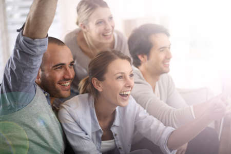 couch: Cheerful group of friends watching football game on tv