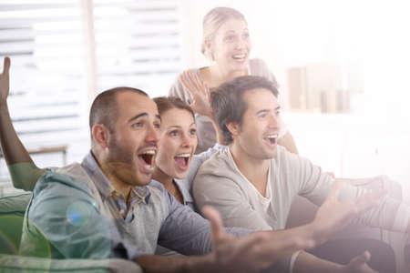 Grupo alegre de amigos viendo el partido de fútbol en la televisión Foto de archivo