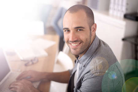 old office: Smiling young man in office working on laptop Stock Photo