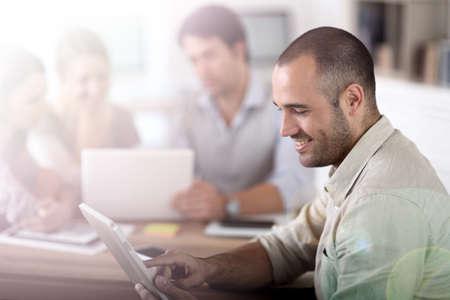 ležérní: Mladý muž v kanceláři pracující na digitální tablety