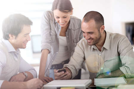People in office laughing at reading text on smartphone photo