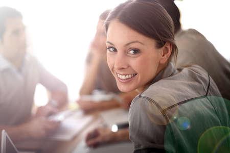 Porträtt av leende arbetar flicka i möte