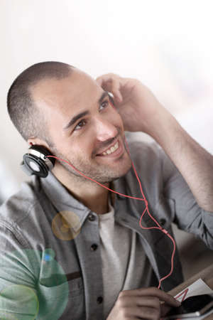 Trendy guy listening to music wiith headset on photo