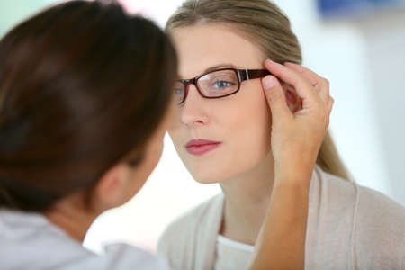 eye exam: Woman trying new eyeglasses with ophtalmologist