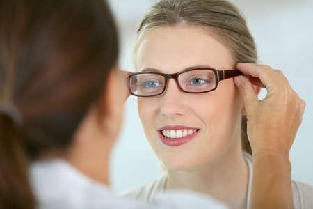 oculista: Mujer que intenta nuevas gafas con oftalmólogo