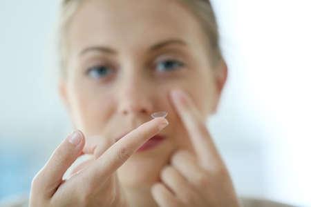 lentes de contacto: Mujer joven que pone en contacto con los ojos lente Foto de archivo