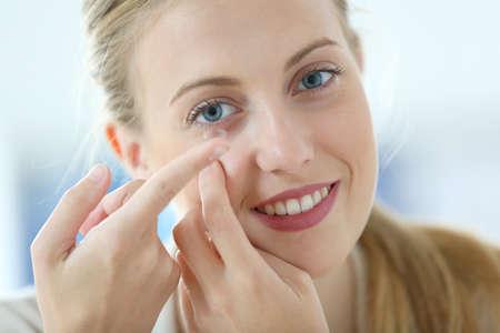 blonde yeux bleus: Jeune femme mettant le contact oculaire lentille sur