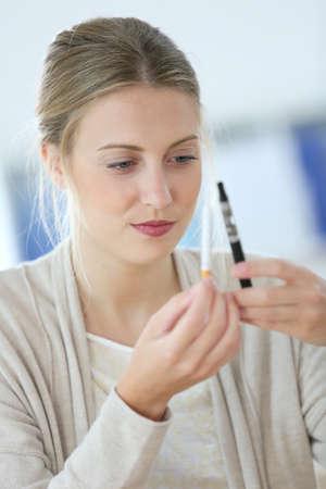 opt: Portret młodej kobiety gotowe do wyboru e-papierosa Zdjęcie Seryjne