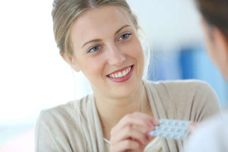 Young woman seing doctor for birth control pills photo