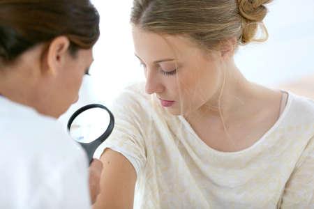 피부 관리에 대한 젊은 여자 보는 의사