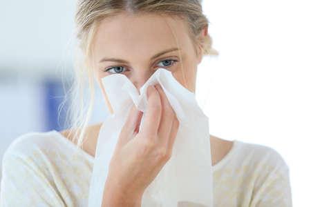 resfriado: Mujer joven con el fr�o que sopla la nariz que moquea