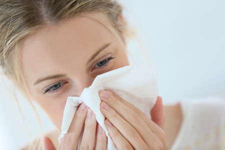 鼻水鼻を吹いている風邪を持つ若い女 写真素材