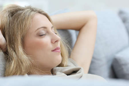 eyes shut: Blond woman in sofa relaxing with eyes shut