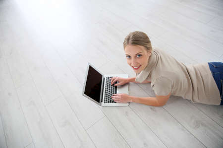 laying down: Young woman laying on wooden flooring with laptop