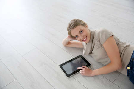 reform: Smiling woman laying on wooden floor with tablet