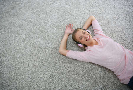 carpet flooring: Blond girl relaxing on carpet floor with headphones on