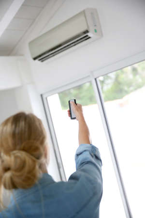 regulating: Woman controlling temperature from air conditioner