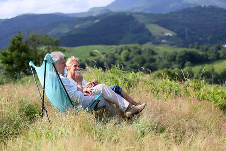 folding chair: Senior couple relaxing in folding chairs in countryside Stock Photo