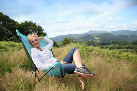 people sitting on chair: Senior woman relaxing in chair in countryside
