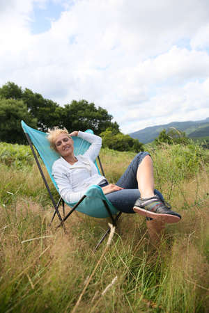 folding chair: Senior woman relaxing in chair in countryside