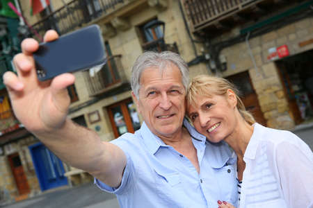 Senior tourists taking picture of themselves with smartphone photo
