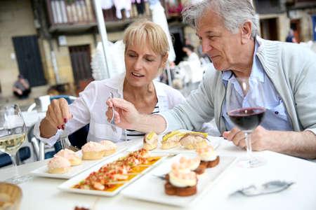 jubilados: Pareja de ancianos comiendo canapés español en España