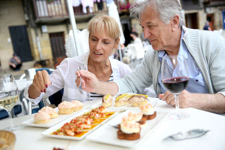 Senior couple eating Spanish fingerfood in Spain photo