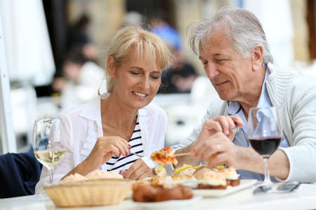 Drinking wine: Senior couple eating Spanish fingerfood in Spain