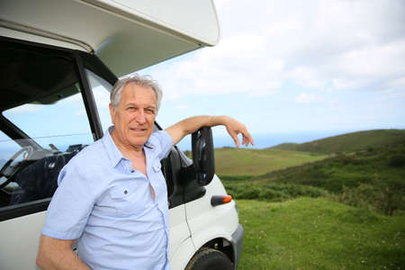 motorhome: Senior man standing by camper, scenery in background