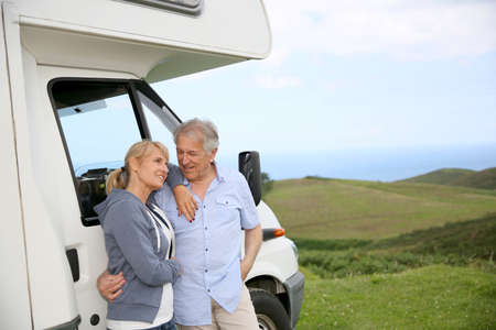 Senior couple standing by motorhome in countryside photo