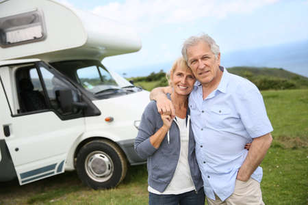 Happy senior couple standing in front of camping car Stock Photo