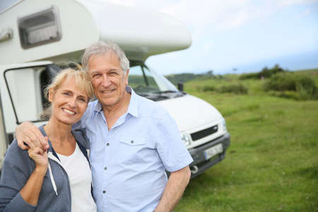 Happy senior couple standing in front of camping car Stockfoto