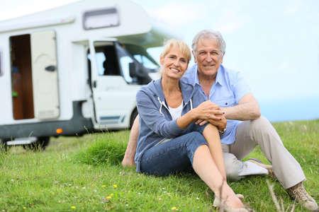 Happy senior couple sitting in grass, camper in background Stockfoto