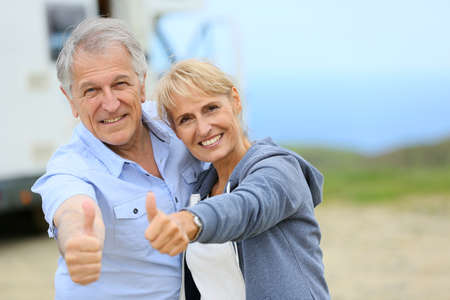 motorhome: Cheerful senior couple standing by camper on road stop