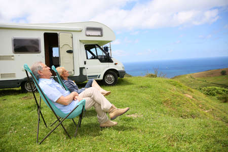 folding: Senior couple relaxing in camping folding chairs, sea landscape Stock Photo