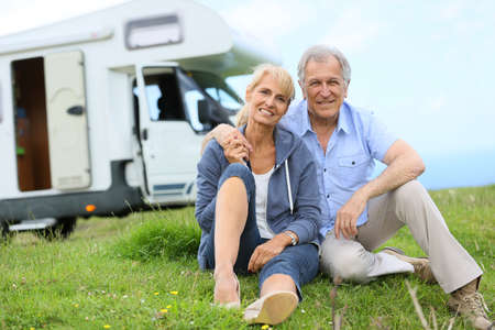 motorhome: Happy senior couple sitting in grass, camper in background Stock Photo