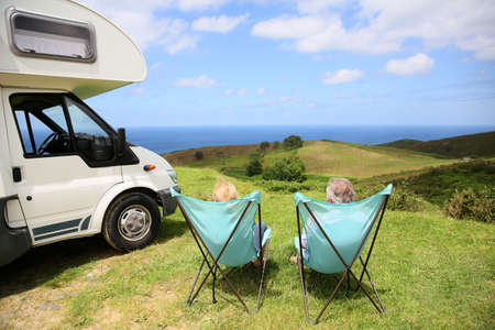 motorhome: Senior couple relaxing in camping folding chairs, sea landscape Stock Photo
